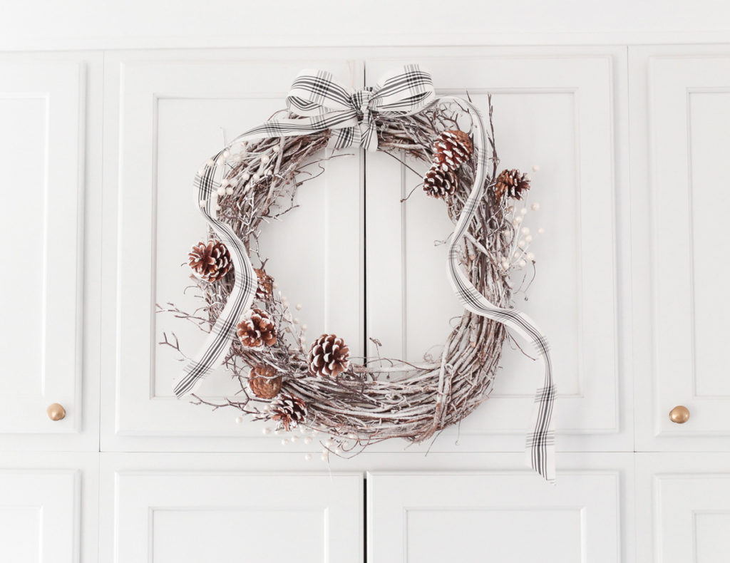 diy white flocked holiday wreath tutorial with pinecones bow